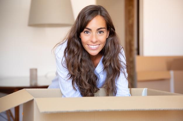 행복 한 젊은 라틴 여자 그녀의 새 아파트에서 물건을 풀고, 판지 상자를 열고, 무료 사진
