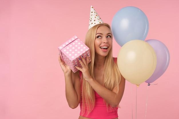 Felice giovane signora bionda dai capelli lunghi che tiene la scatola incartata e chiedendosi cosa c'è dentro, si rallegra della bella festa insieme agli amici, in piedi su sfondo rosa e mongolfiere multicolori Foto Gratuite