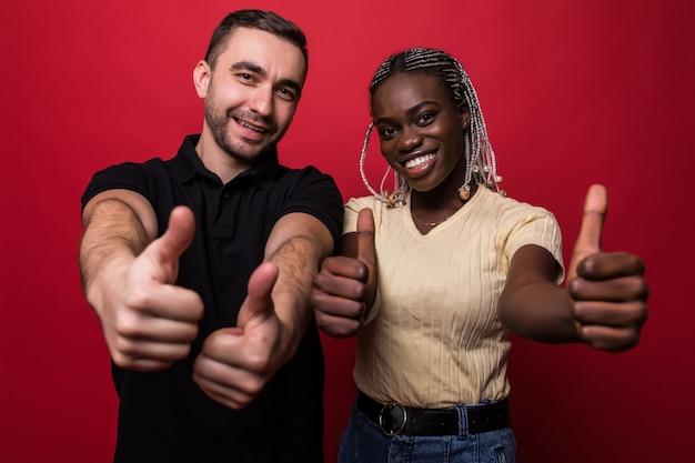 Счастливая молодая прекрасная межрасовая пара показывает палец вверх и смотрит в камеру на красном фоне Premium Фотографии