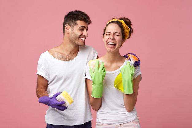 幸せな若い男性が食器を洗うのを好まない保護手袋で必死のストレス女性を慰める。片付けを嫌う悲しい泣いているガールフレンドを笑ってハンサムな肯定的な男性 無料写真