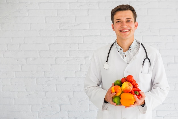 Happy young male doctor standing against the wall holding fresh fruits and vegetable Free Photo