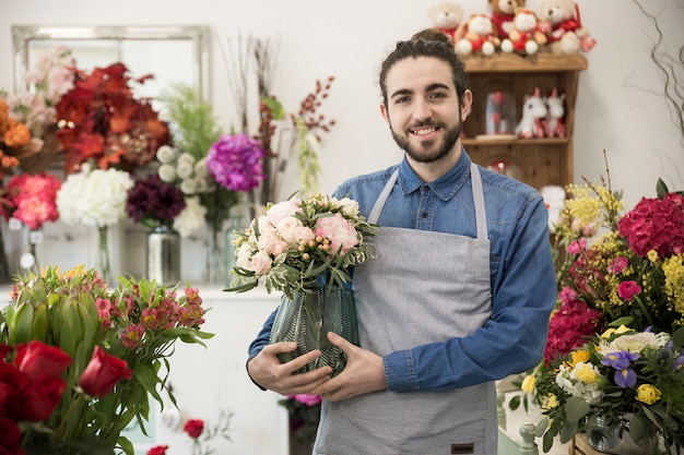 Happy young male florist holding flower vase in hand standing in the flower shop Free Photo
