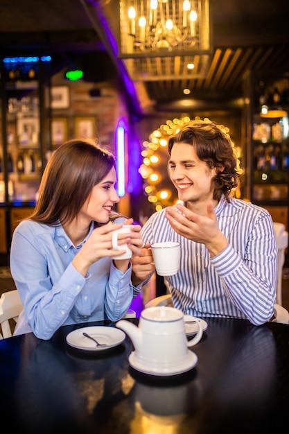 幸せな若い男と女のカフェでお茶を飲む Premium写真