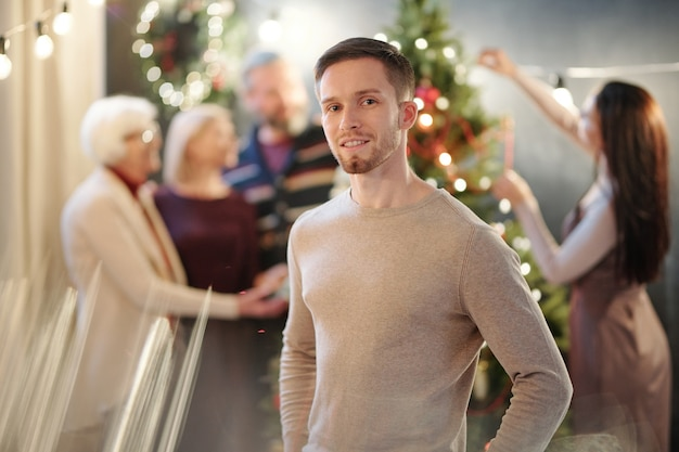 Happy young man in beige pullover standing with women decorating firtree before xmas Premium Photo