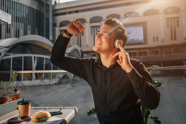 Happy young man cheering. he sits at table outside and wave with fists. guy enjoying listening to music. sun is shining. Premium Photo