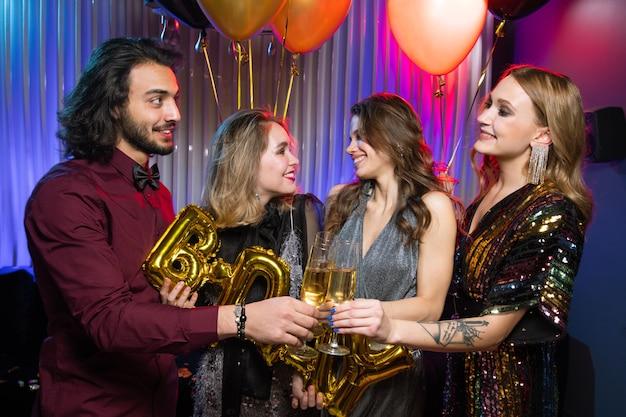 두 여자 친구의 배경에 생일 파티에서 여자 중 하나와 샴페인의 플루트를 부딪 치는 행복 한 젊은 남자 프리미엄 사진