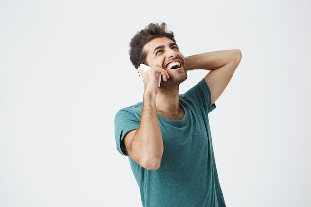 Happy young man feeling excited, happy and laughing while talking on the phone. stylish hipster communicating with his girlfriend over smart phone with smile Free Photo