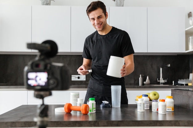 Happy young man filming his video blog episode Free Photo
