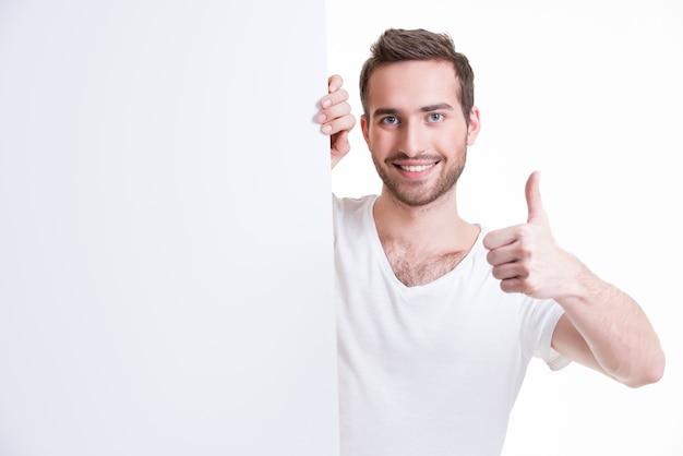 Il giovane felice osserva fuori dall'insegna in bianco con il pollice in su - isolato su bianco Foto Gratuite