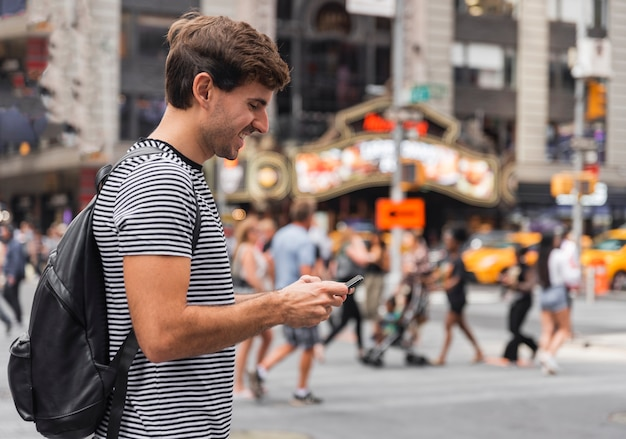 Happy young man looking at a smartphone Free Photo