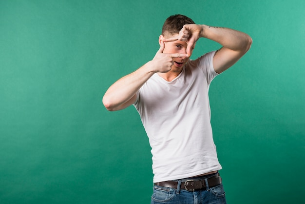 Happy young man looking through a frame formed by his hands against green background Free Photo