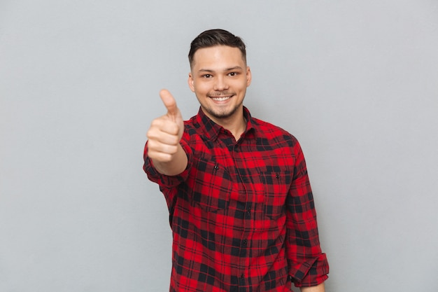 Happy young man make thumbs up gesture. Free Photo