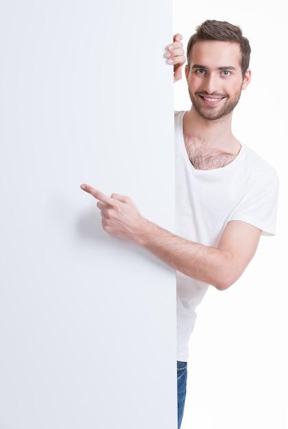 幸せな若い男は空白のバナーに指を指す-白で隔離 無料写真