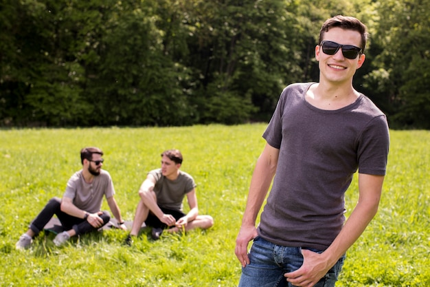 Happy young man posing on meadow with friends Free Photo