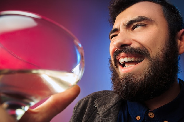 The happy young man posing with glass of wine. emotional male face. view from the glass. the party, christmas, alcohol, celebration event concept Free Photo