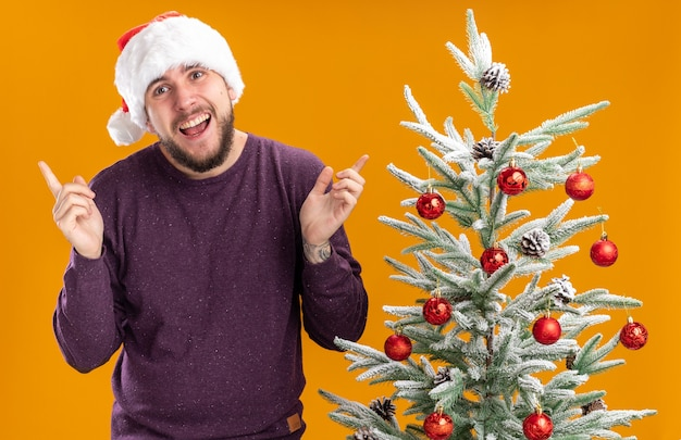 Felice giovane uomo in maglione viola e santa hat guardando la fotocamera con il sorriso sul viso con le braccia alzate in piedi accanto all'albero di natale su sfondo arancione Foto Gratuite