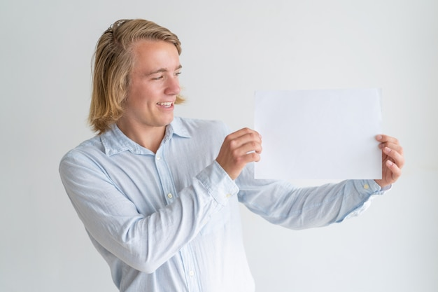 Happy young man showing blank sheet of paper Free Photo