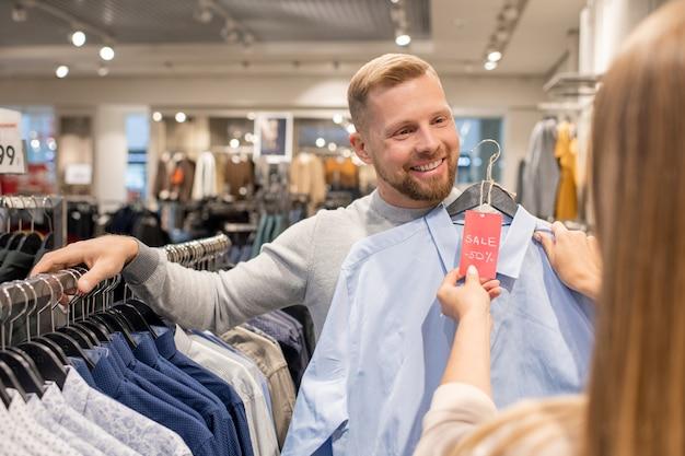 カジュアルウェア部門のラックで立っている間50パーセント割引で彼のガールフレンドの青いシャツを示す幸せな若い男 Premium写真