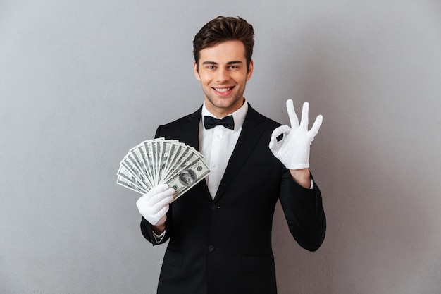 Happy young man showing okay gesture holding money. Free Photo