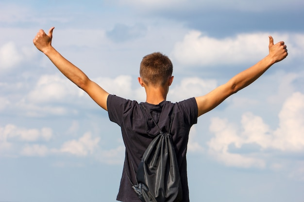 Happy young man standing on top with his hands up Premium Photo