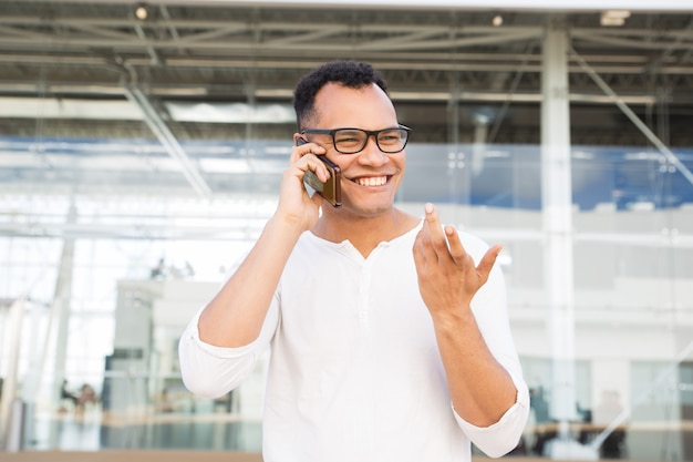 Happy young man talking on smartphone and gesturing outdoors Free Photo