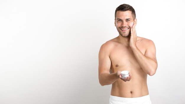 Happy young man using cream on his face against white wall Free Photo
