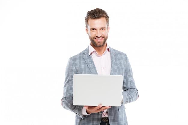 Счастливый молодой человек, используя портативный компьютер Бесплатные Фотографии