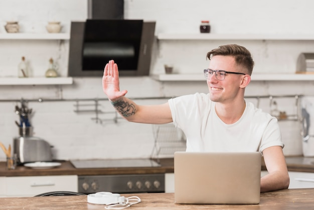 Happy young man waving his hand with laptop on table in the kitchen Free Photo