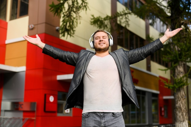 Happy young man with headphones raising his hands in sides Free Photo