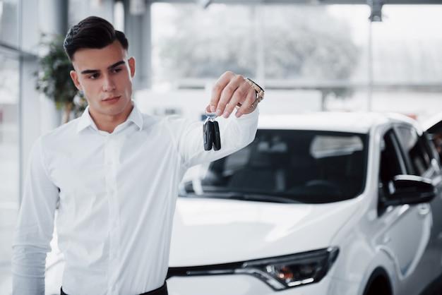Felice giovane con le chiavi in mano, fortunato comprare una macchina Foto Gratuite