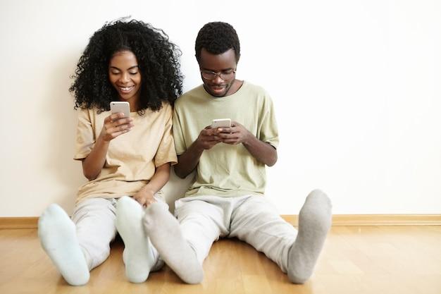 Счастливая молодая супружеская пара, отдыхая дома на деревянном полу с гаджетами. красивая девушка пишет друзьям в социальных сетях, пока ее муж сидит рядом с ней Бесплатные Фотографии