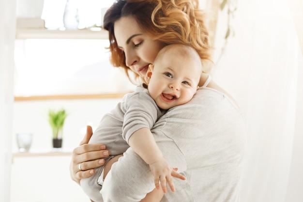 행복 한 젊은 엄마는 소중한 작은 아이를 보유하고 부드럽게 그의 작은 몸을 포옹. 아이가 즐겁게 웃고 큰 회색 눈을 가진 카메라를보고. 무료 사진