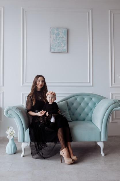Счастливая молодая мама на стильном диване отдохнуть с маленькой дочкой в черных платьях и позирует, улыбающиеся мать и женщина ребенок весело провести время в студии. семейный вид Premium Фотографии