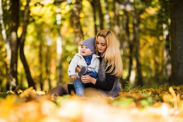 幸せな若い母親と幼い息子が秋の公園で時間を過ごします。 無料写真