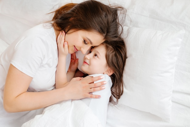 Happy young mother hugs her little daughter in bed Premium Photo