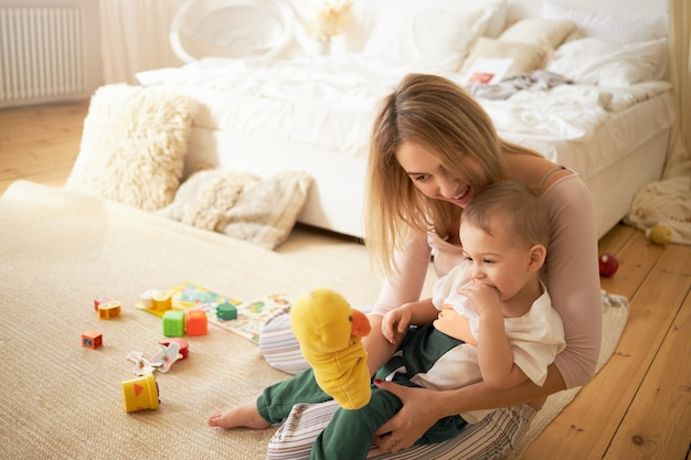 Happy young mother playing and cute little child playing on floor. blonde female babysitting adorable infant sitting on carpet in bedroom holding yellow duck toy. motherhood and childcare concept Free Photo