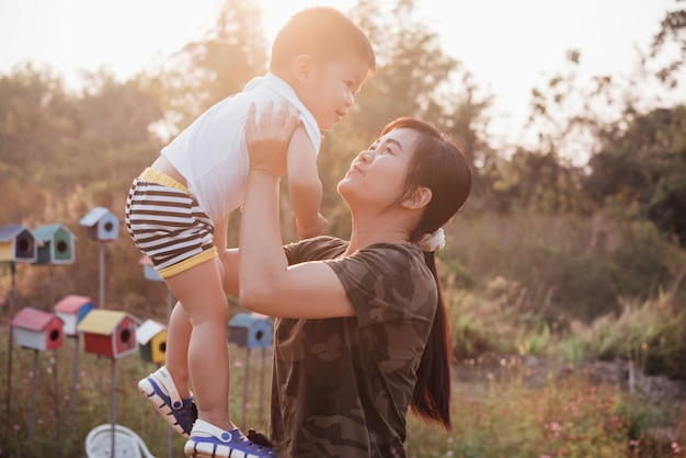 Happy young mother playing and having fun with her little baby son in the park on a sunny summer day Free Photo