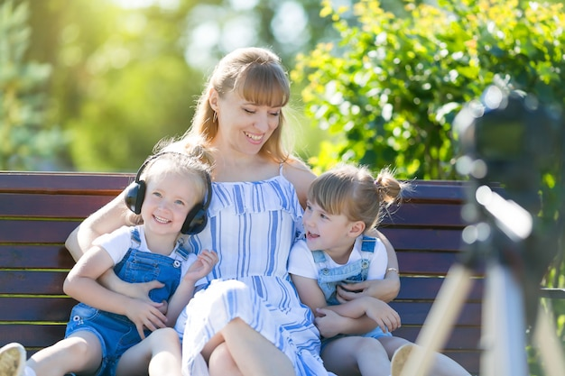 Happy young mother with children in front of a video camera. Premium Photo