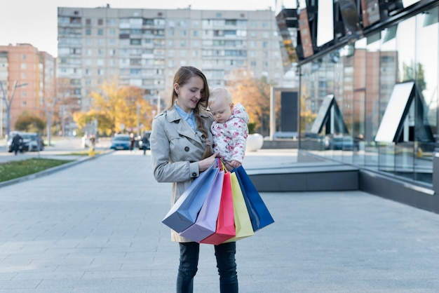 Happy young mother with little daughter on the arms and shopping bags in hand. Premium Photo