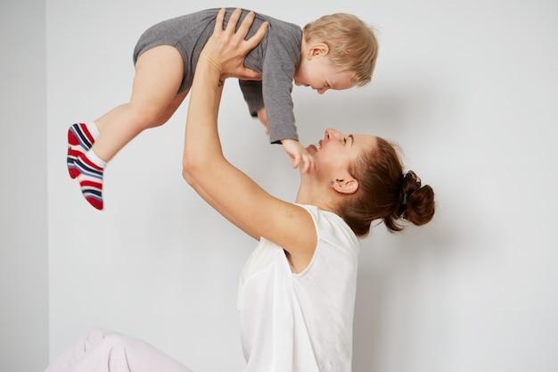 Felice giovane madre con il piccolo figlio a casa Foto Gratuite