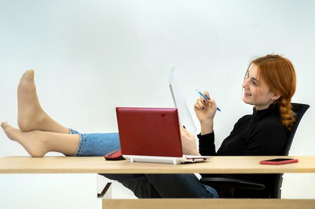 Счастливый молодой офисный работник женщина сидит спокойно с ногами на столе за рабочим столом с ноутбуком Premium Фотографии