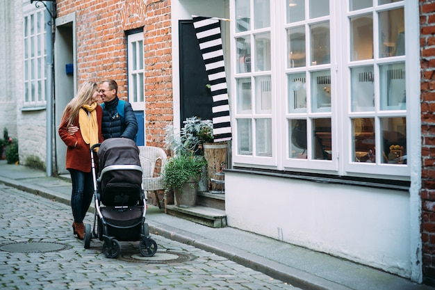 Happy young parents with baby stroller in the street of lubeck (germany) Premium Photo