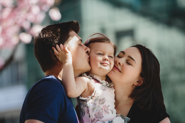 Happy young parents with a little daughter stand under blooming pink tree outside Free Photo
