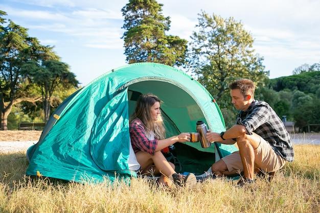 Счастливые молодые люди разбили лагерь на лужайке и сидят в палатке. двое путешественников и друзей пьют чай из термоса. женщина, держащая полюс. походный туризм, приключения и концепция летних каникул Бесплатные Фотографии