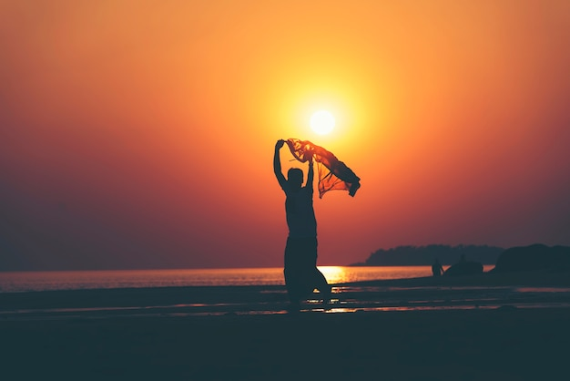 Happy young people dancing and spraying at the beach on beautiful summer sunset Premium Photo