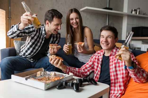Счастливые молодые люди едят пиццу, пьют пиво, веселятся, вечеринка друзей дома, хипстерская компания вместе, двое мужчин и одна женщина, улыбаются, позитивно, расслаблены, болтаются, смеются, Бесплатные Фотографии