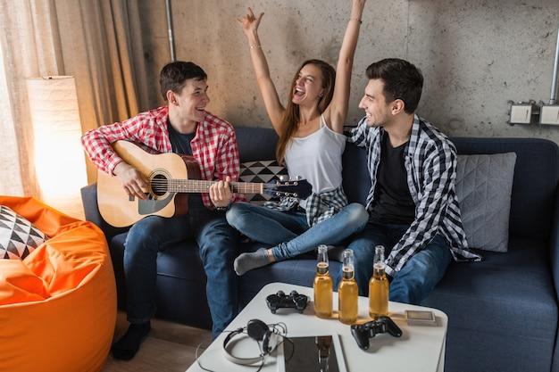 Счастливые молодые люди веселятся, вечеринка друзей дома, хипстерская компания вместе, двое мужчин и одна женщина, играют на гитаре, улыбаются, позитивно, расслаблены, пьют пиво Бесплатные Фотографии
