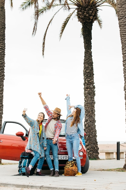 Happy young people taking selfie near red car in street Free Photo