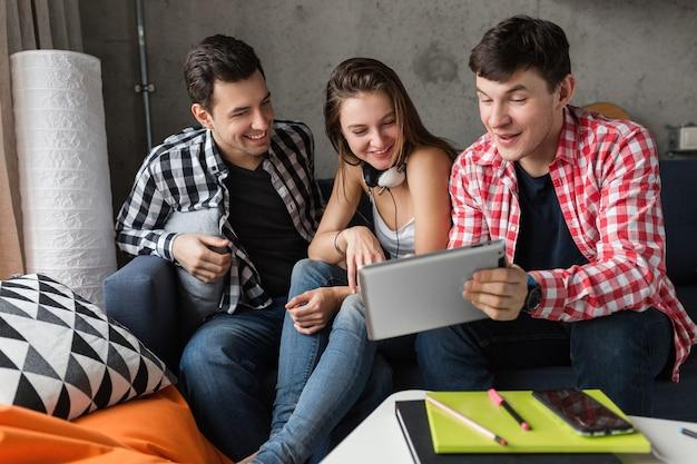 Giovani felici che utilizzano tablet, studenti che imparano, si divertono, amici fanno festa a casa, compagnia hipster insieme, due uomini una donna, sorridente, positivo, educazione online Foto Gratuite