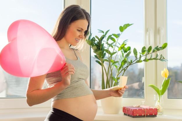 ギフト用の箱とハートのバルーンで幸せな若い妊婦 Premium写真
